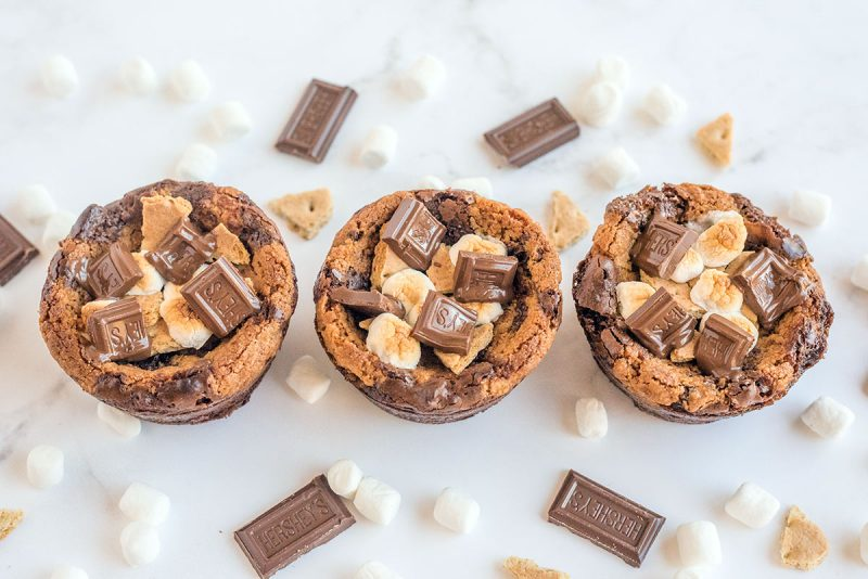 Three S\'mores Brookie Bowls in a row surrounded by mini marshmallows, Hershey\'s bars and broken graham crackers