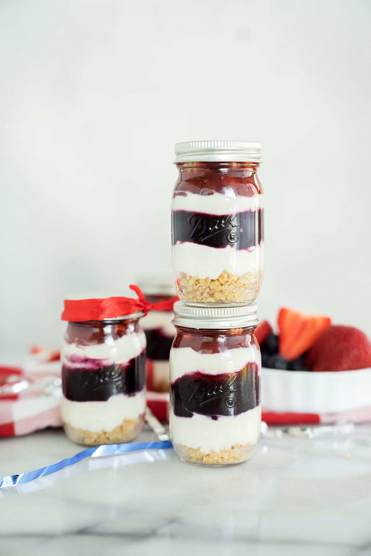 several no-bake red white and blue min i cheesecake in mason jars with fresh berries on top
