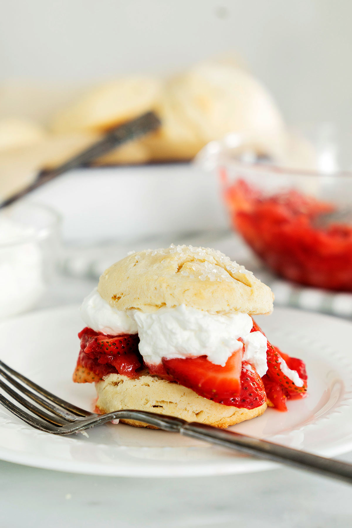 a white plate with a classic strawberry shortcake made with macerated strawberries, sweet whipped cream and biscuits