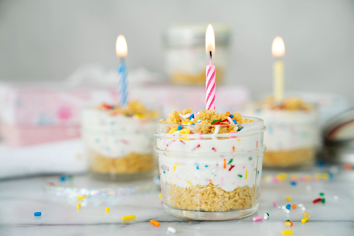 mini birthday cake cheesecake in a jar with lit birthday candles for garnish