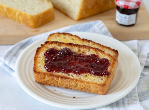 Two slices of English muffin bread, one with jam, on a white plate. A loaf of English muffin bread on a cutting board with raspberry jam in the background.