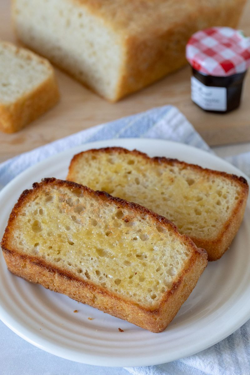 Two slices of buttered English muffin bread on a white plate. A loaf of English muffin bread on a cutting board with raspberry jam in the background.