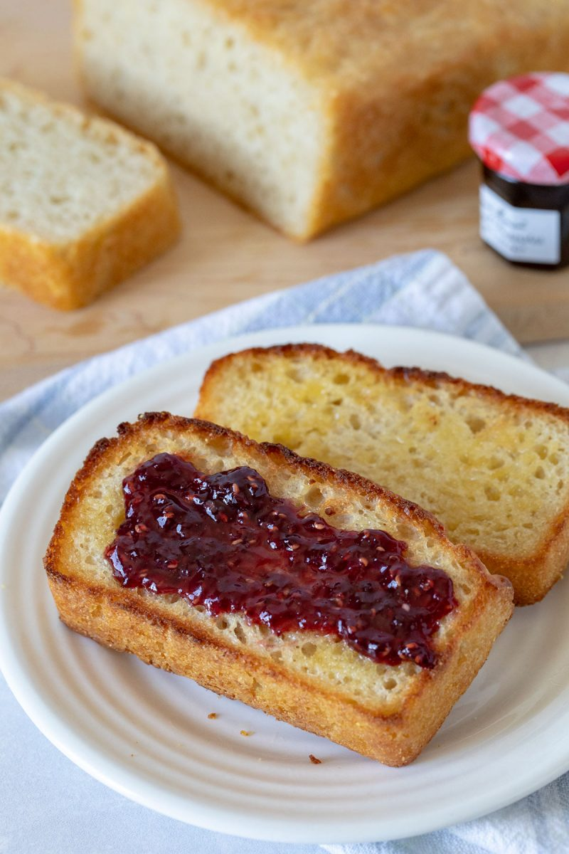 Two slices of English muffin bread, one with jam, on a white plate.