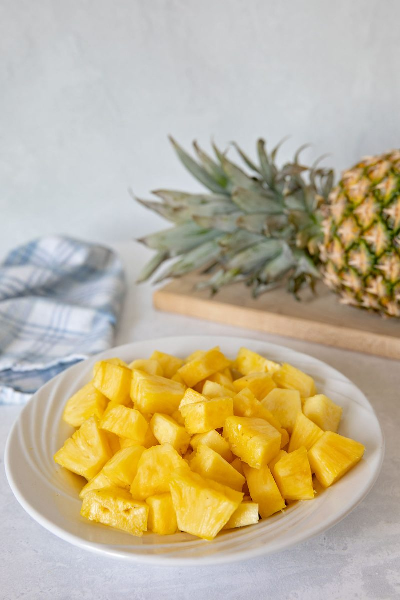cut up pineapple chunks in a white bowl with a whole pineapple on a cutting board in the background