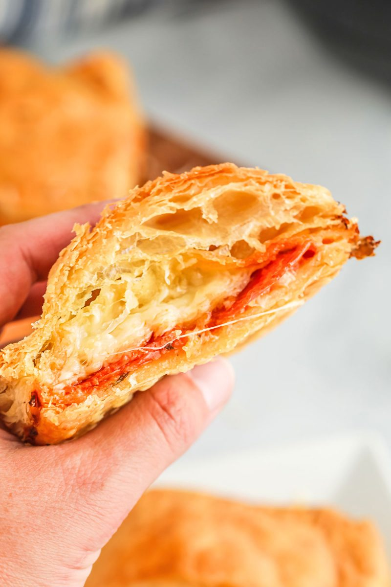 holding half of an air fryer pizza pocket with cheese, sauce and pepperoni