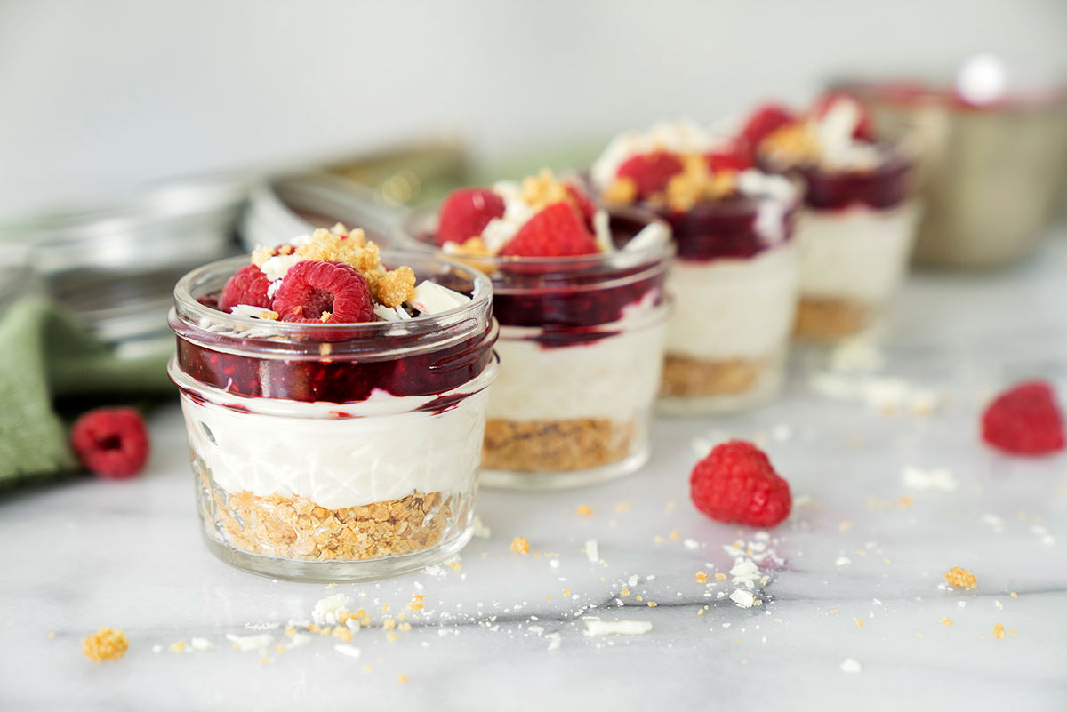 mini mason jars filled with white chocoalte raspberry cheesecake and fresh raspberries lined up on a marble counter