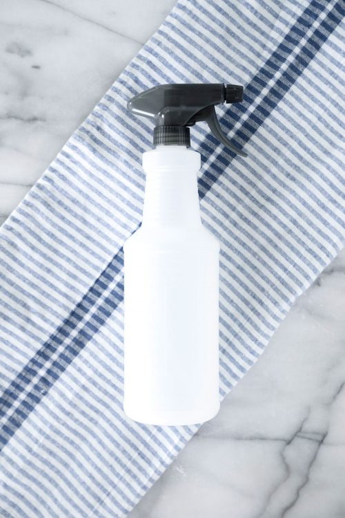 spray bottle on a blue striped napkin