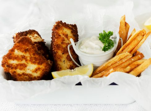 halibut fish and chips in a white tin with parchment paper