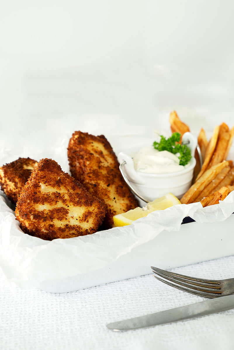 white tin with halibut fish and chips and lemon and tartar sauce