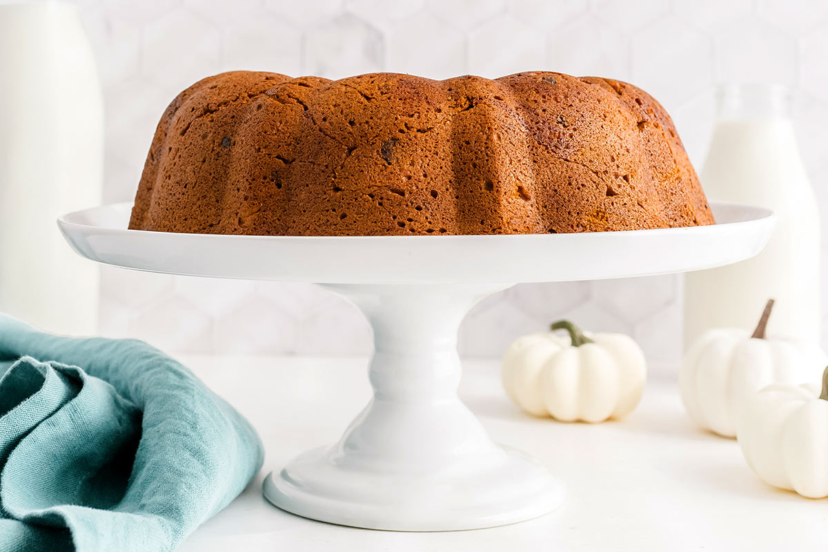 cake stand with a whole pumpkin bundt cake