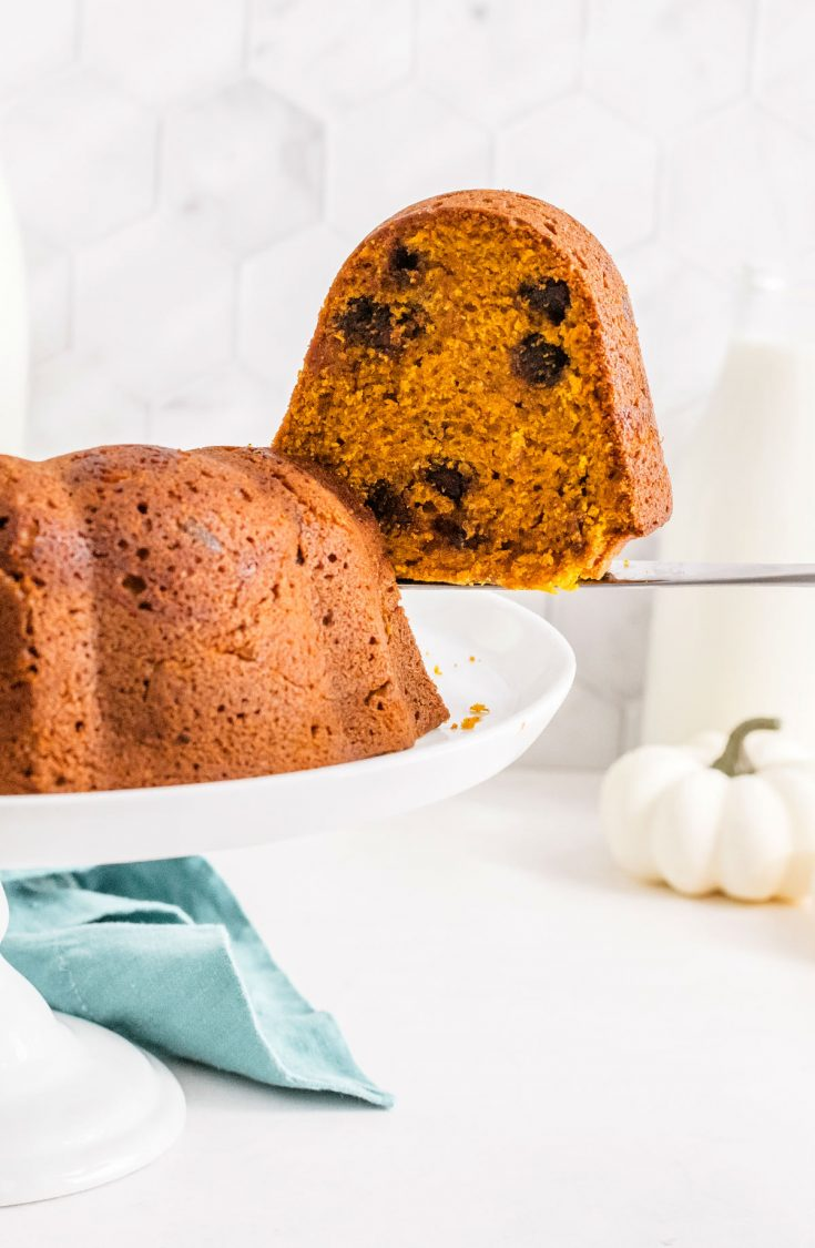 slice of pumpkin chocolate chip bundt cake on a white cake stand