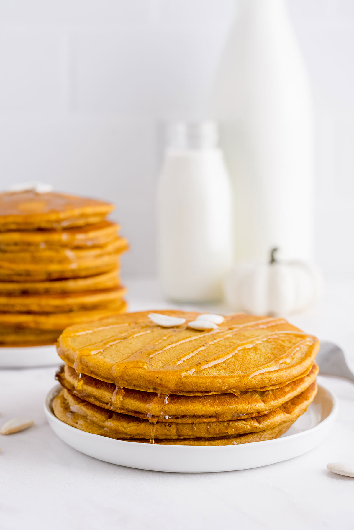 short stack of three fluffy pumpkin pancakes on a table with more pancakes in the background
