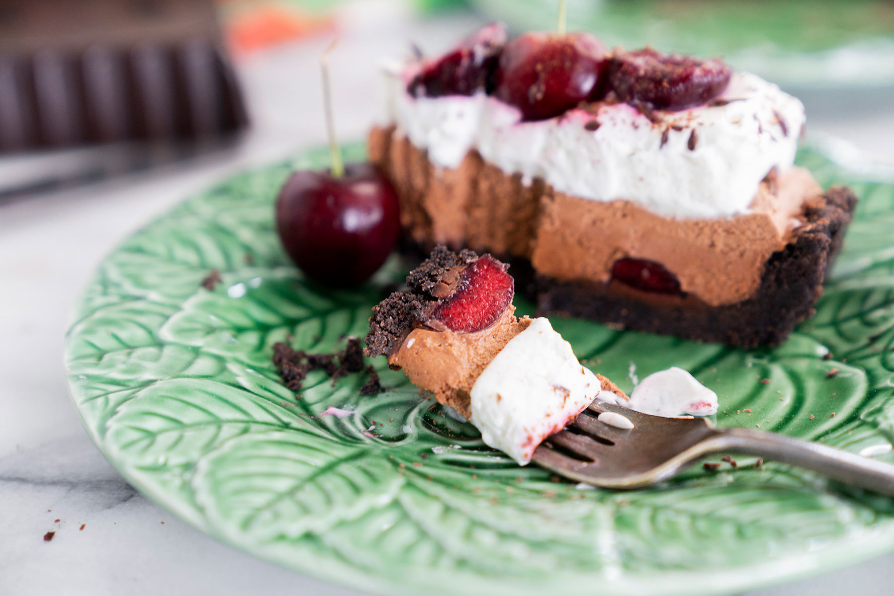 slice of black forest tart with fresh cherries and whipped cream with a bite taken out on a green plate