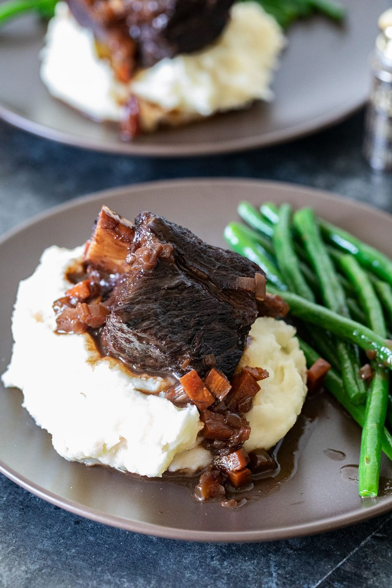 braised beef short ribs on a plate with mashed potatoes and green beans