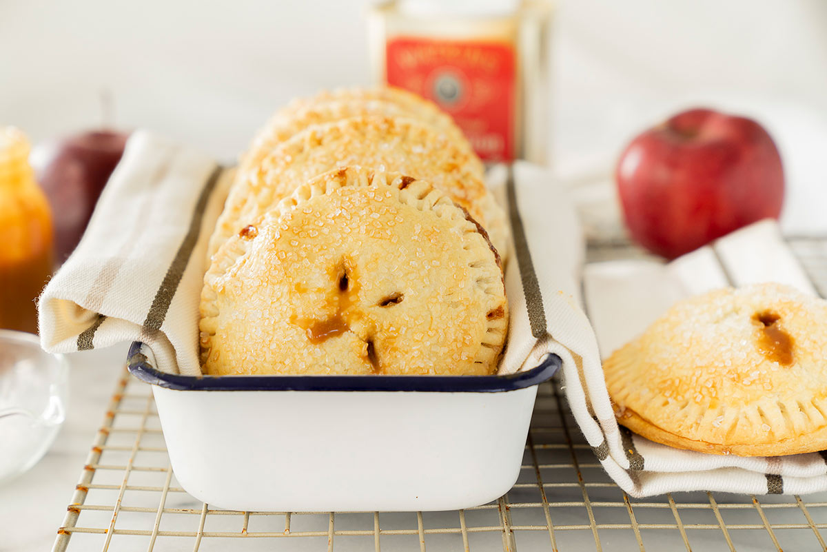 caramel apple hand pies in a white tin on a wire rack