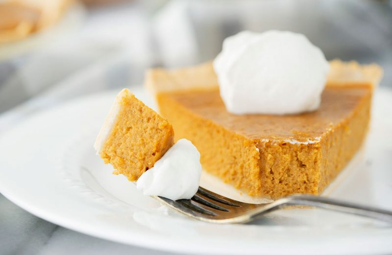 plate of pumpkin pie slice with whipped cream