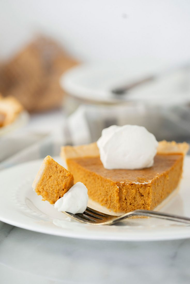 slice of pumpkin pie with whipped cream on a white plate