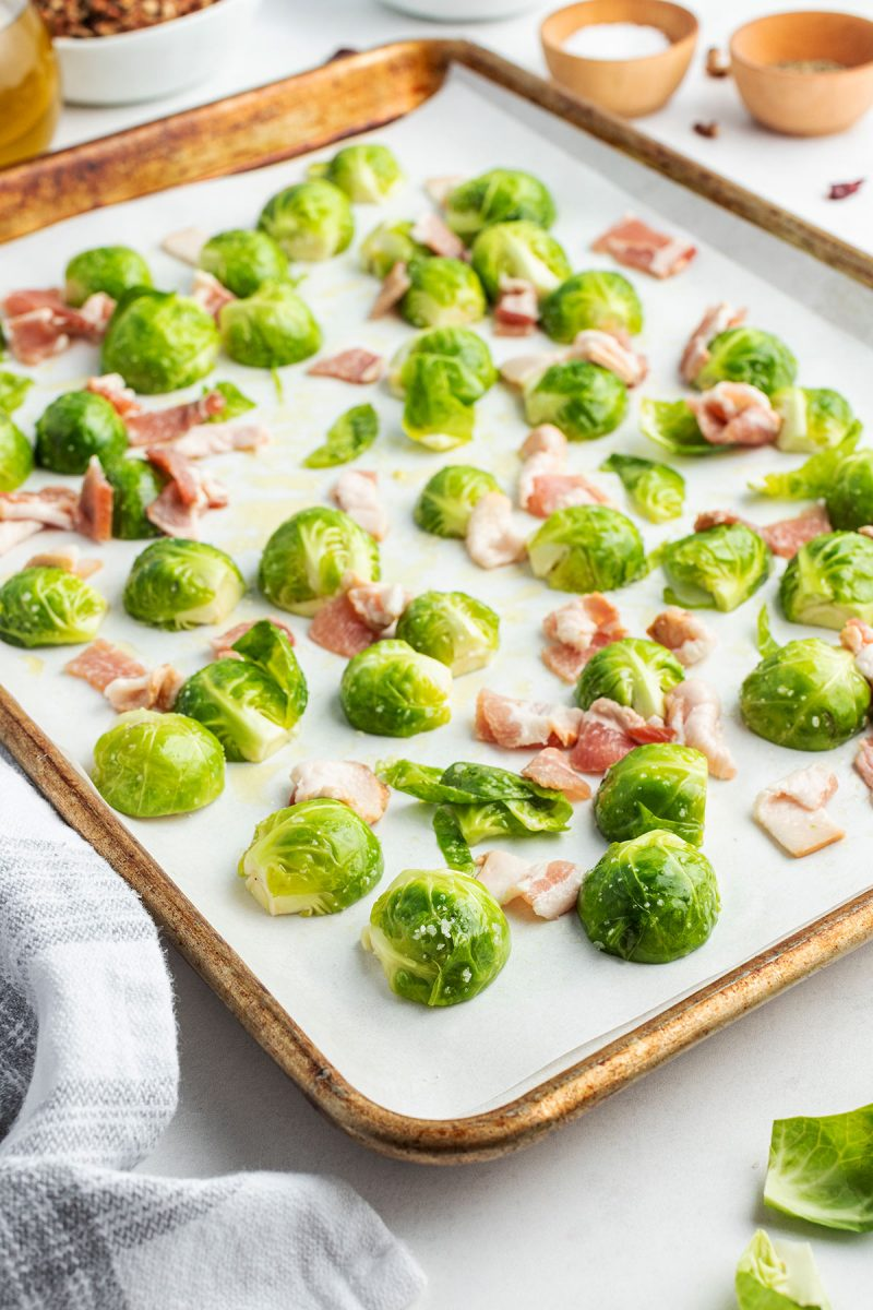 uncooked brussel sprouts on a baking sheet with bacon pieces