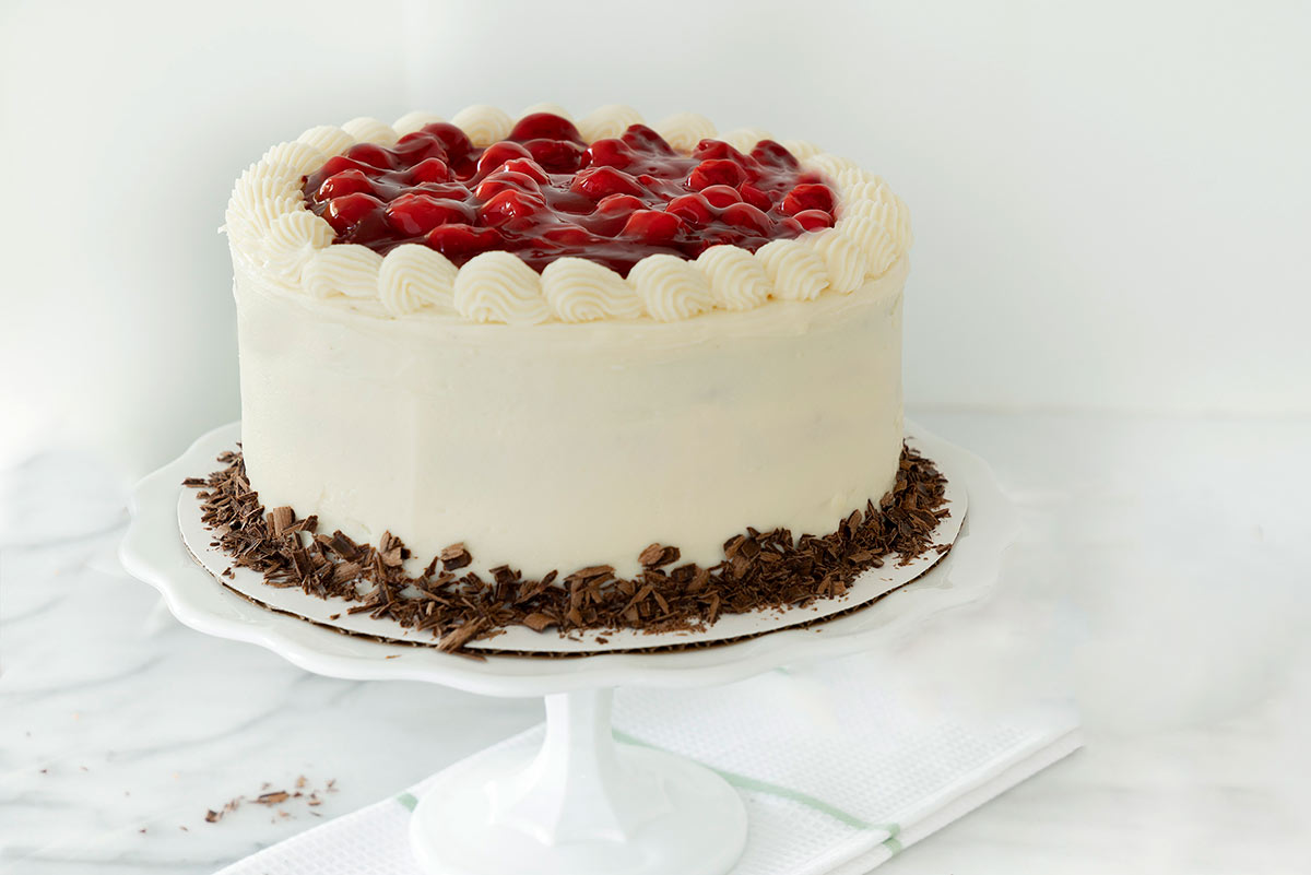 three layer black forest cake with cherries on top