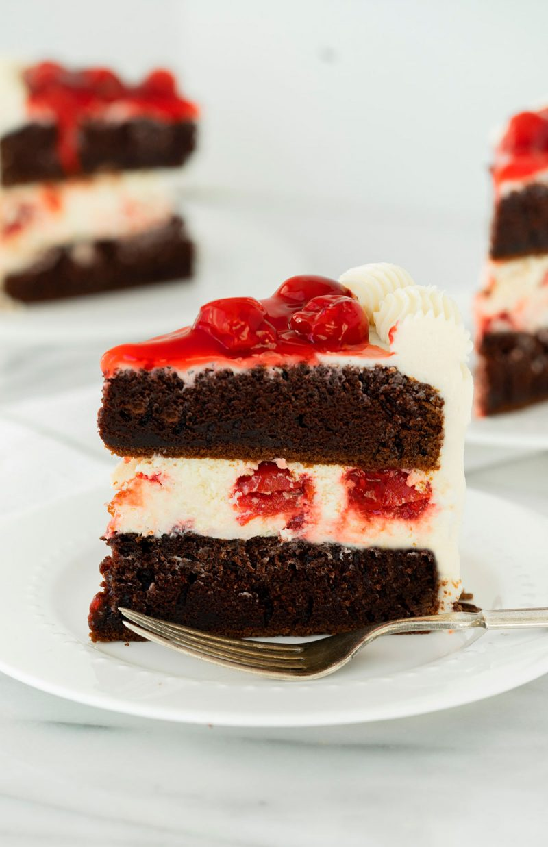 slice of black forest cheesecake cake with cherry pie filling