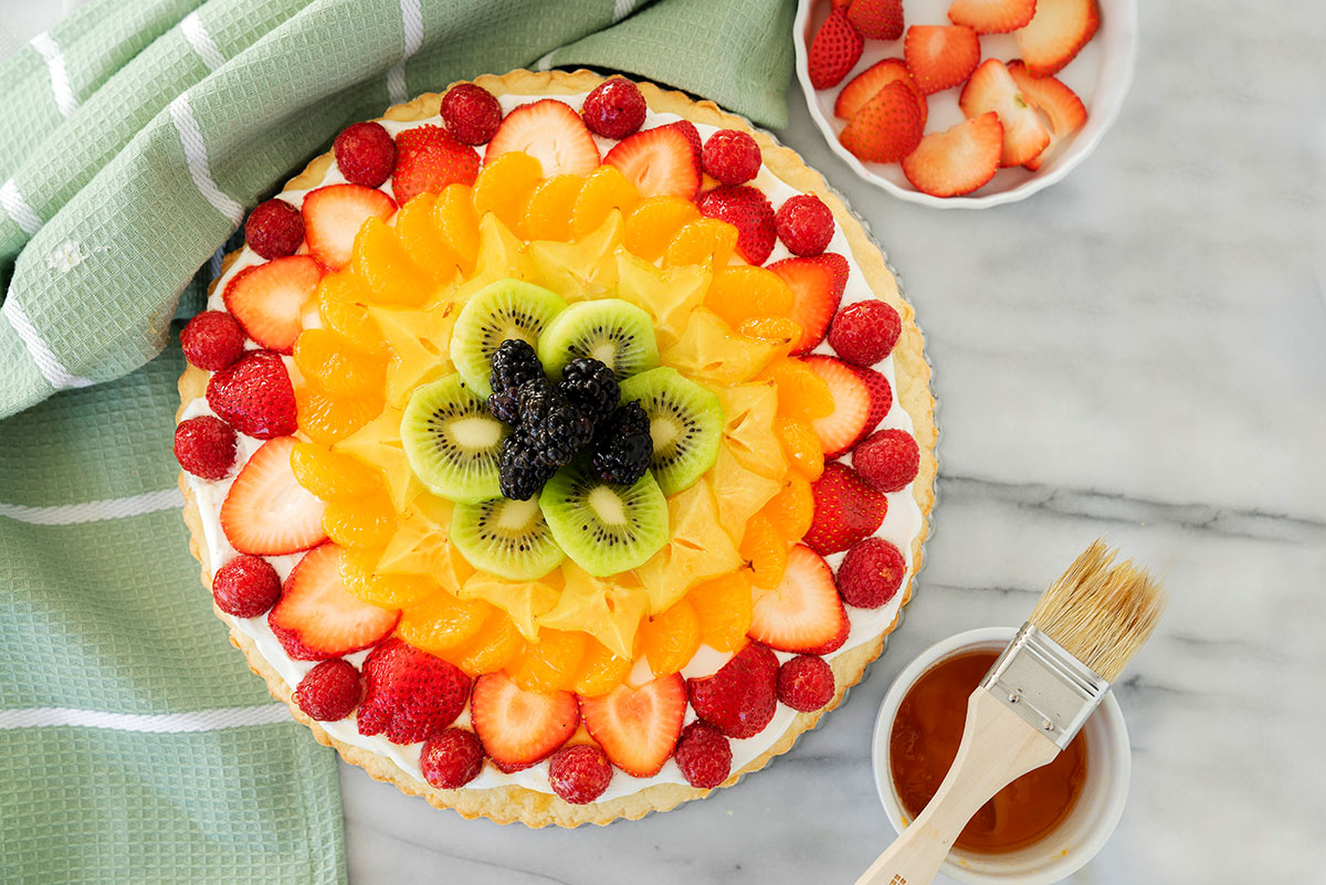 fruit pizza with fresh berries and sliced fruit on a cookie crust