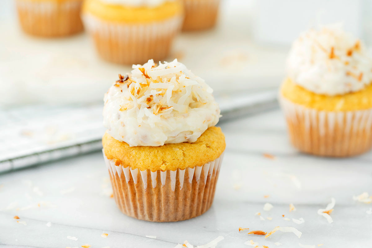 coconut cupcake with toasted coconut frosting on a marble countertop