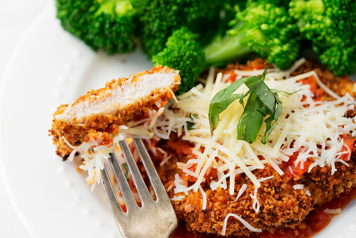 sliced of lighter chicken parmesan with panko breadcrumbs and broccoli