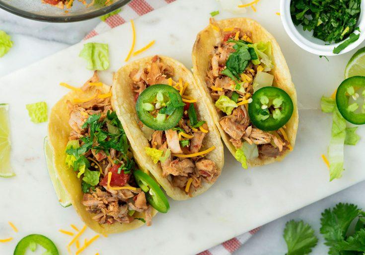 three pork carnitas tacos in hard shells with green jalapenos