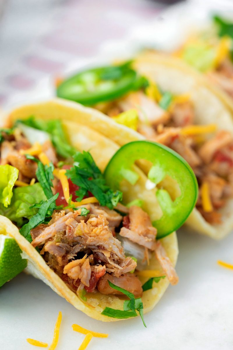 close up on a taco with shredded pork and raw veggie toppings
