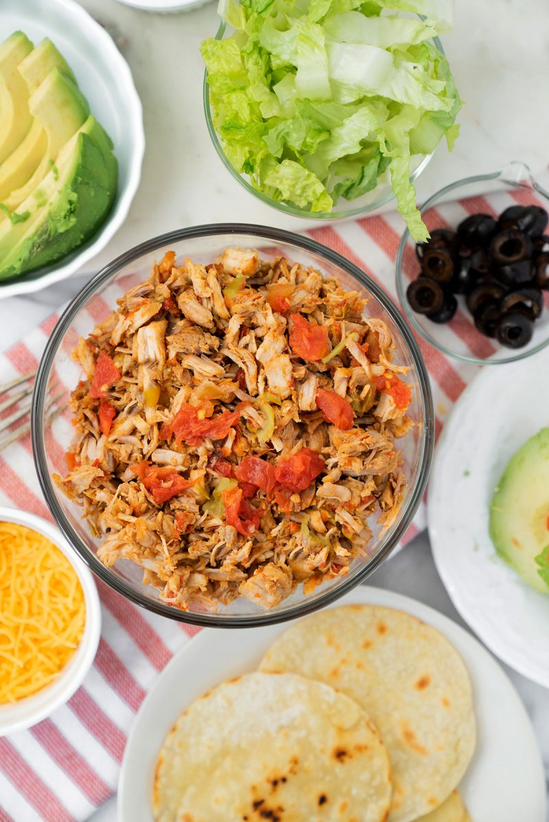 bowl of pork carnitas with taco toppings and tortillas