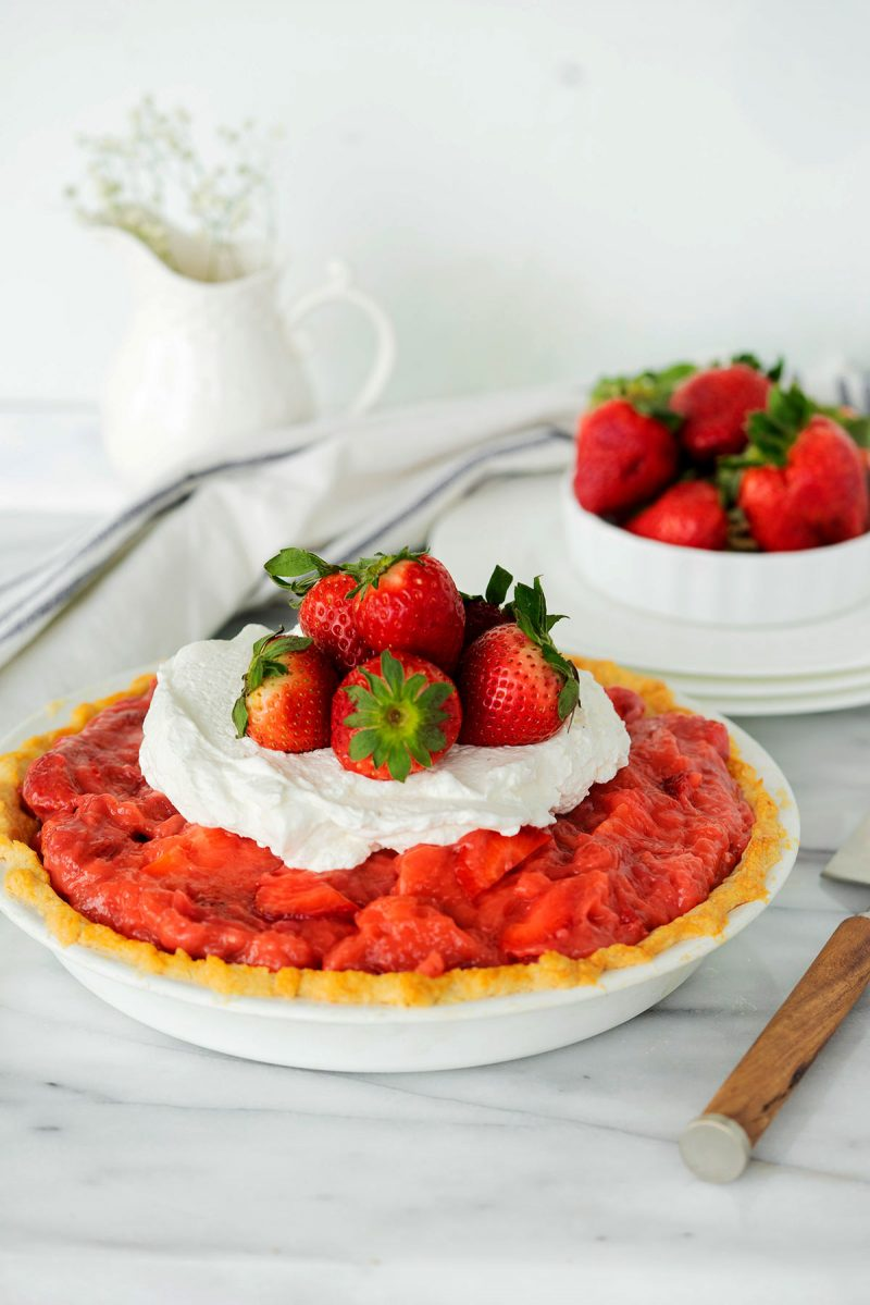 whole fresh strawberry pie with whipped cream on top