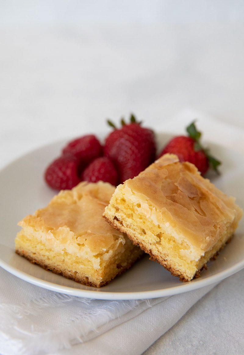 two slices of gooey butter cake with fresh strawberries on a plate