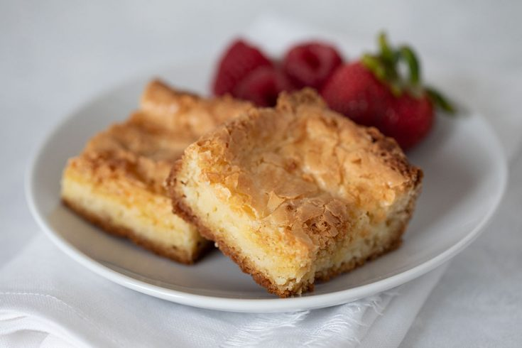 two slices of gooey butter neiman marcus cake on a plate with strawberries