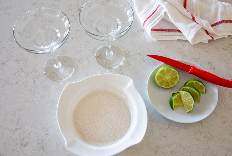 overhead of two glasses and sugar on a plate with lime to decorate the rims