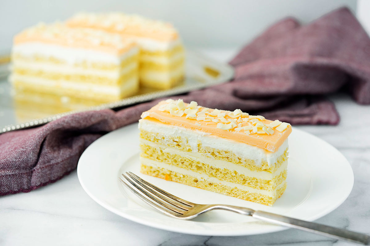 slice of orange layer cake with buttercream on a white plage