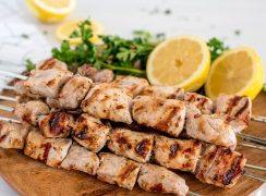 wooden plate with greek pork on skewers with lemon