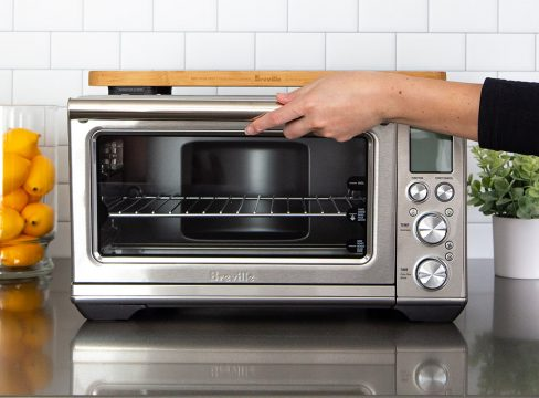 A hand opening the oven door for the Breville Smart Oven Air Fryer