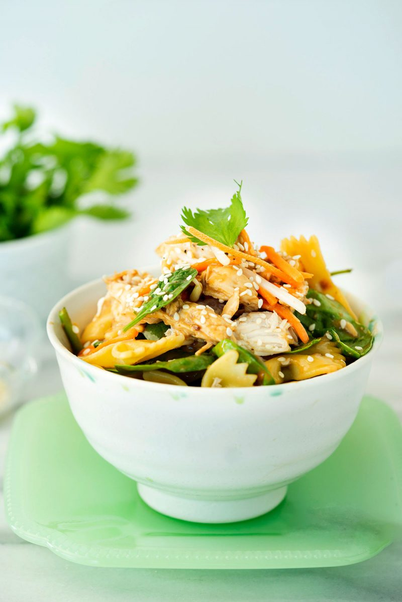 white bowl of asian spinach and pasta salad with carrots