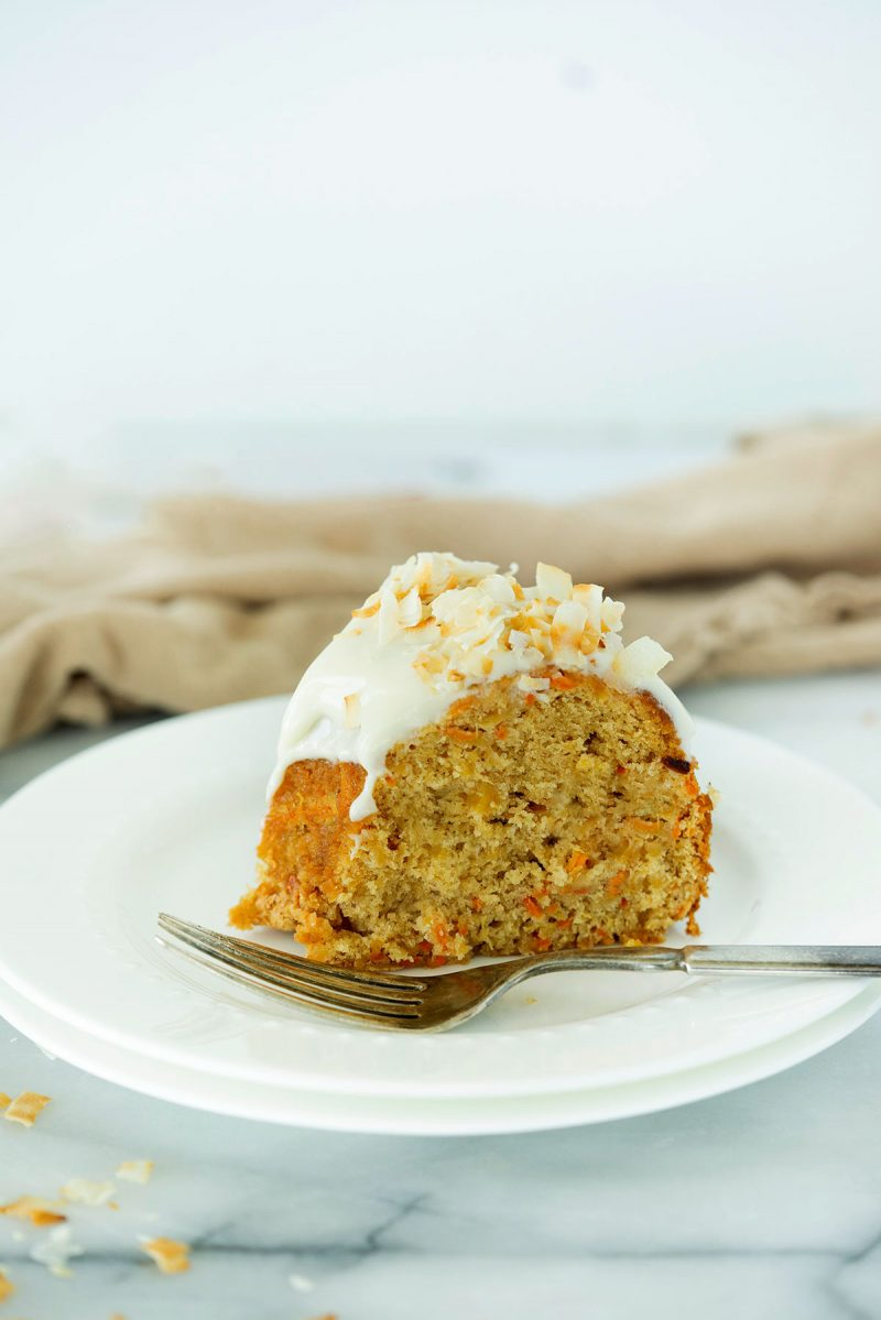slice of carrot and pineapple cake on a plate with a fork