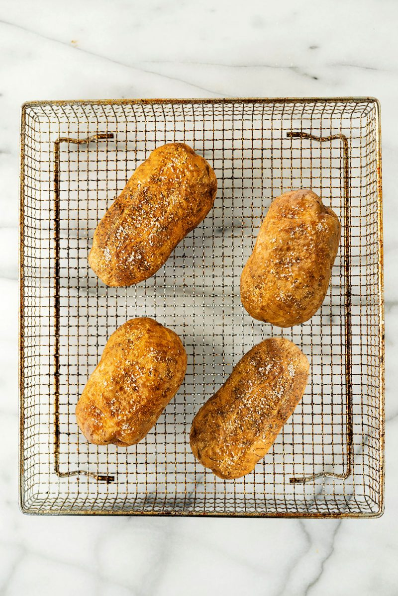 wire rack with four baked potatoes from an air fryer