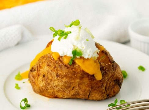 baked air fried potato on a white plate with cheese, sour cream and scallions