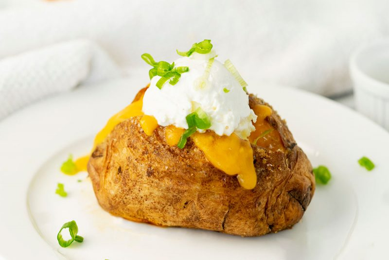 white plate with a baked potato with sour cream, cheese and scallions