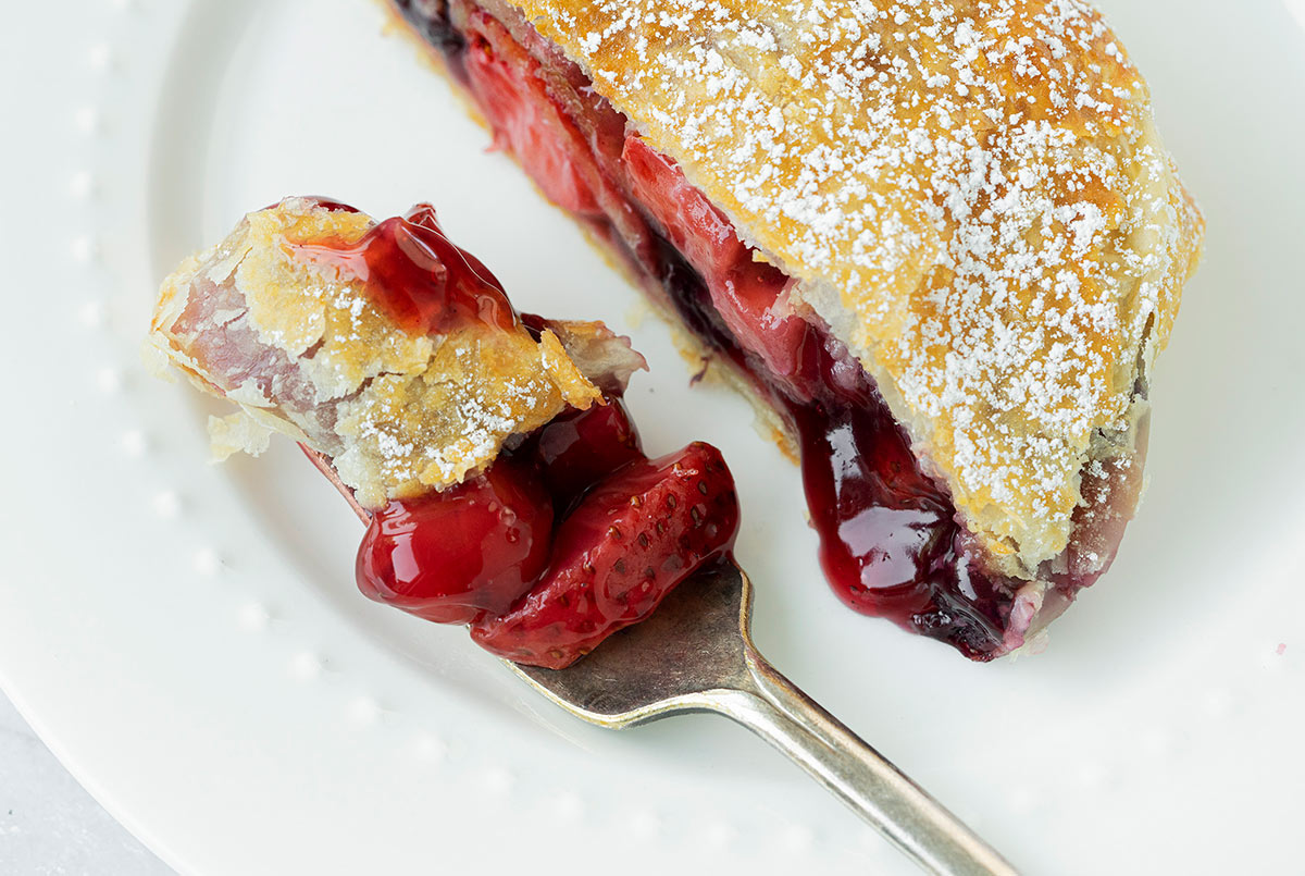 apple and berry strudel with  a slice removed
