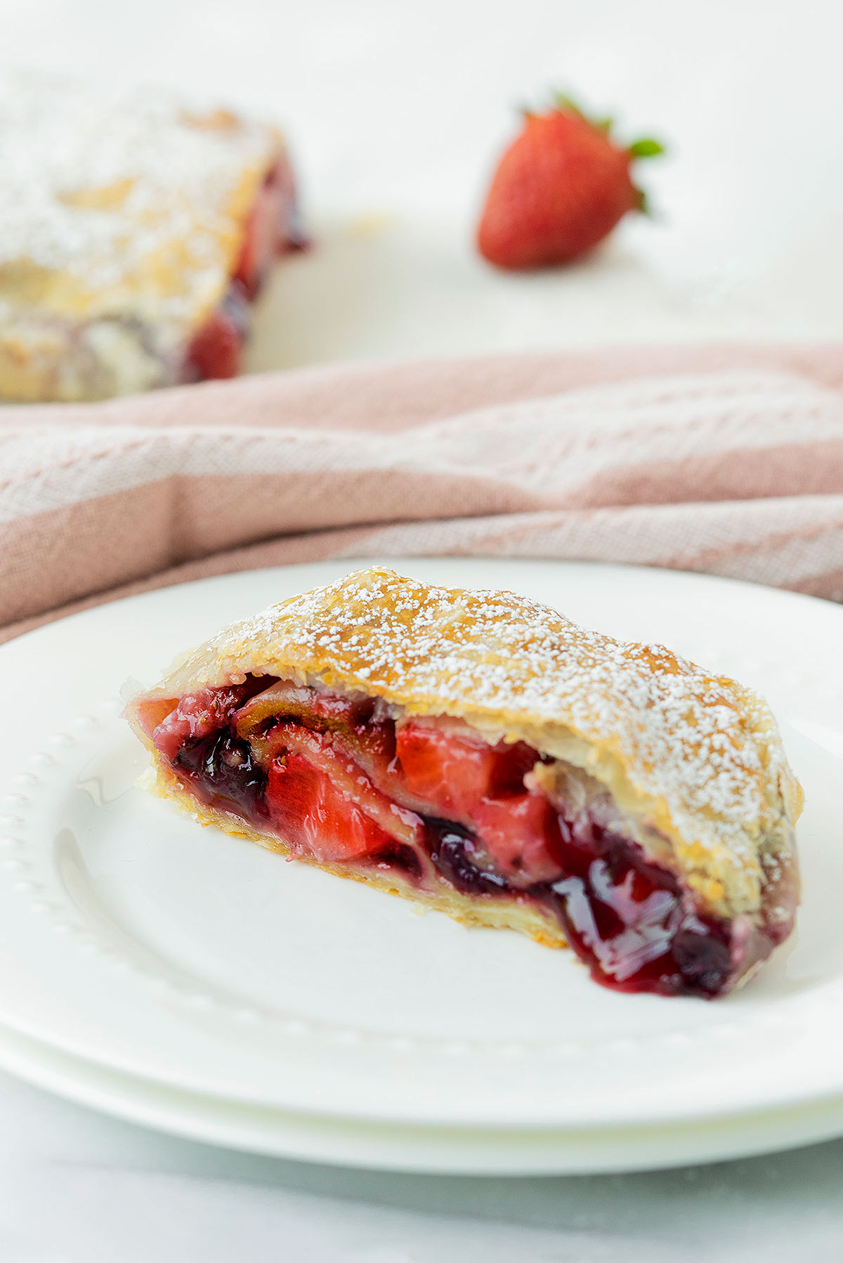 slcie of apple berry strudel on a white plate