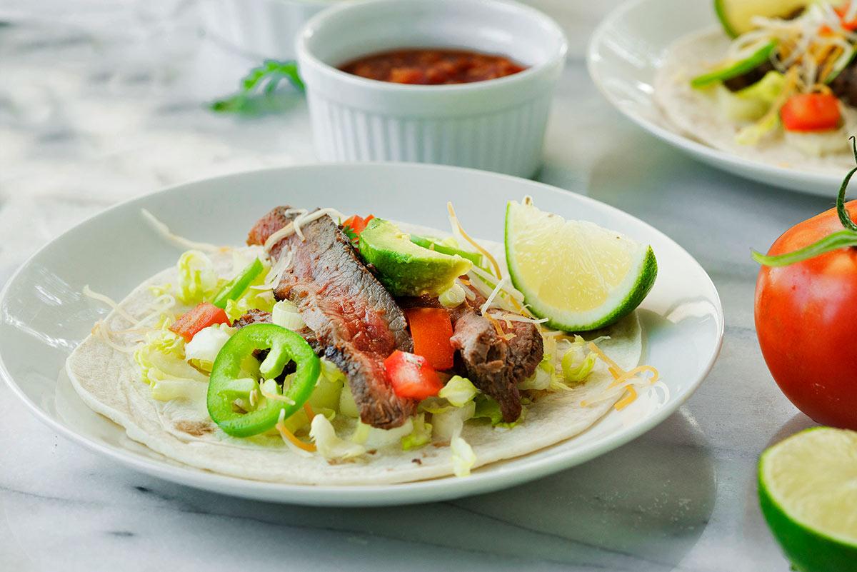 carne asada taco on a plate with lime and jalapeno