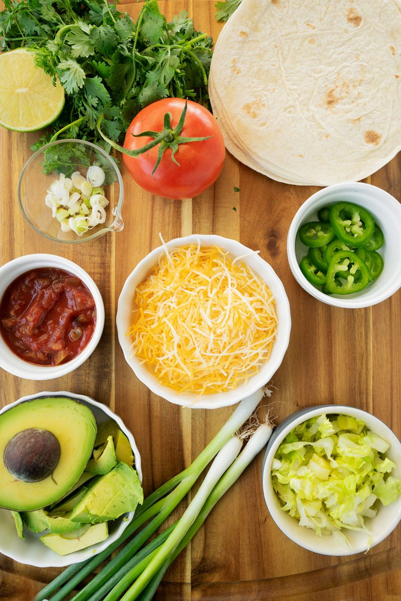 toppings on a wooden board with cheese, avocado, tomato, tortillas and scallions