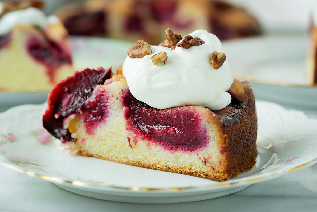 slice of a plum cake with whipped cream on top
