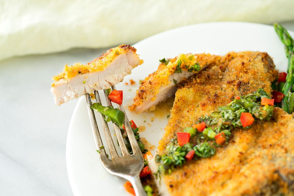 sliced open crispy pork chop with chimichurri sauce