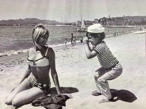 Bambino guarda attraverso un cannocchiale sulla spiaggia, 1950