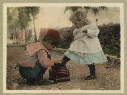 Un ragazzino lucida le scarpe a una bambina. Senza data